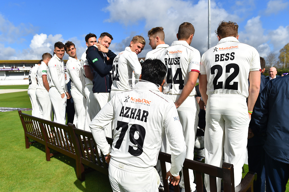 Azhar Ali of Somerset hides behind the players in their County Championship whites while the team photo with an alcoholic drinks sign is shot during the 2019 media day at Somerset County Cricket Club at the Cooper Associates County Ground, Taunton, United Kingdom on 2 April 2019.