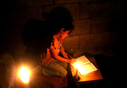 April 25, 2017 - Gaza City, The Gaza Strip, Palestine - Palestinian refugee girls studying by candlelight in his family's temporary home during the power outage in the Jabalya refugee camp in the northern Gaza Strip, 25 April 2017. (Credit Image: © Mahmoud Issa/Quds Net News via ZUMA Wire)