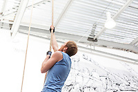 Side view of dedicated man climbing rope in crossfit gym