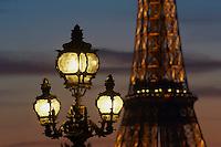 France, Paris (75), llampadaire avec la Tour Eiffel illuminée (SETE-illuminations Pierre Bideau) en arrière-plan // France, Paris, Paris light and Eiffel Tower at night