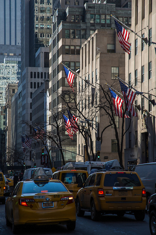 Flags of the United States blow in the wind displayed outside the Rockefeller Centre buildings, 610 5th Avenue, Midtown, Manhattan, New York City, New York, United States of America.  Busy traffic drives along 5th Avenue including the classic New York yellow taxi.  (photo by Andrew Aitchison / In pictures via Getty Images)