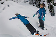 Kids playig in snow while snowshoeing through forest in winter, Calaveras Big Trees State Park, Calaveras County, California