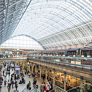 Shops and eateries in the main concourse under the distinctive iron and glass arched cover over the platforms of St Pancras Railway Station (now known as St Pancras International). The renovated station features distinctive Victorian architecture and serves as a Eurostar terminal for high-speed trains to Europe. There are also platforms for domestic train services. The distinctive train shed roof was designed by William Henry Barlow.