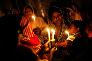 Indian Catholics take part in a late night Easter mass at the Our Sister of Charity church in the town of Raikia in the state of Orissa, India, April 12, 2009. Tensions remain high in the area several months after violence by Hindu fundamentalist towards the Christian minority forced thousands from their homes and leaving several churches and thousands homes across the state destroyed.