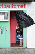 young female person in an photo booth while curtain is blown away