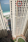 Dubai<br /> Nerves of steel or completely mad! What it takes to be a window cleaner in Dubai<br /> <br /> It's one thing building some of the world's tallest towers. But what happens when the windows need cleaning?<br /> Perched on a narrow sill hundreds of feet above the ground, this chap demonstrates nerves of steel as he gives the windows of a 34th floor apartment in Dubai's Jumeirah Beach the once-over with a long handled brush - without a safety harness.<br /> As he takes his life into his hands, at least he has the sense to hold on to the window frame, even if it is by his fingertips, as he goes about his task.<br /> He was snapped making sure the windows were sparkling by a resident in a neighbouring apartment block.<br /> <br /> When it comes to safety among its massive immigrant workforce, the Dubai authorities have a dubious record.<br /> Conditions in which immigrants are expected to work has been a subject of discussion in the United Arab Emirates for many years.<br /> Yet the majority of these employees have no voice, especially when it comes to their own safety. They are also aware that, if they are deported, there are thousands of others willing to take their place.<br /> Photo Shows: Hell for leather: Stretching a point: The window cleaner uses a long-handled brush to reach the corners<br /> ©Exclusivepix
