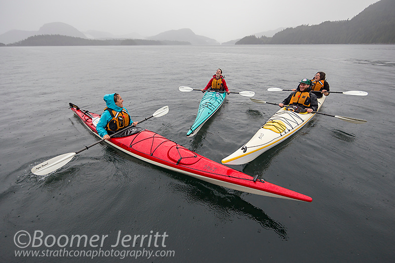 Friends share a laugh during a rainstorm, kayaking in the Discovery Islands, near Quadra Island.  Northern Gulf Islands, British Columbia, Canada
