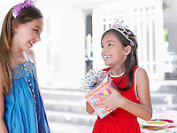Two girls (7-9 10-12) at birthday party one holding present smiling