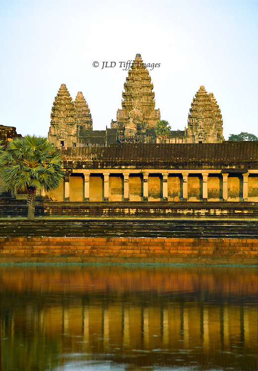 Vertical format view across moat in which temple towers are reflected.