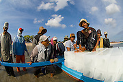 Fishermen prepare for a night of fishing by taking blocks of ice to their boat. The ice is used to preserve their catch in the intense tropical heat.