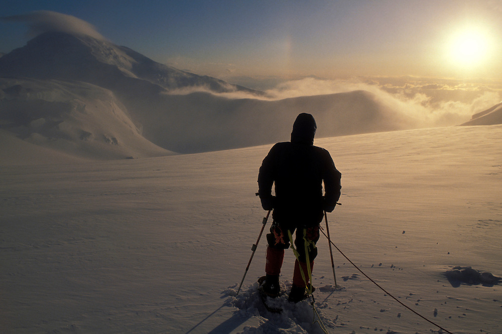 USA, Alaska, Denali National Park, (MR) Rick Ford watches sunset on Kahiltna Glacier during Mt McKinley expedition