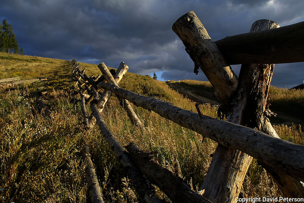 A hand-built fence climbs a grassy hill near Frazier, Colorado in the autumn of 2003.