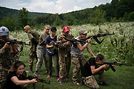 "In this July 29, 2018 photo, young participants of the ""Temper of will"" summer camp, organized by the nationalist Svoboda party, practice tactical formations with AK-47 assault riffles in a village near Ternopil, Ukraine."