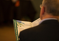 An audience member reads through the summary of financiall statement during LRGHealthcare annual meeting at Laconia Country Club on Wednesday evening.  (Karen Bobotas/for the Laconia Daily Sun)