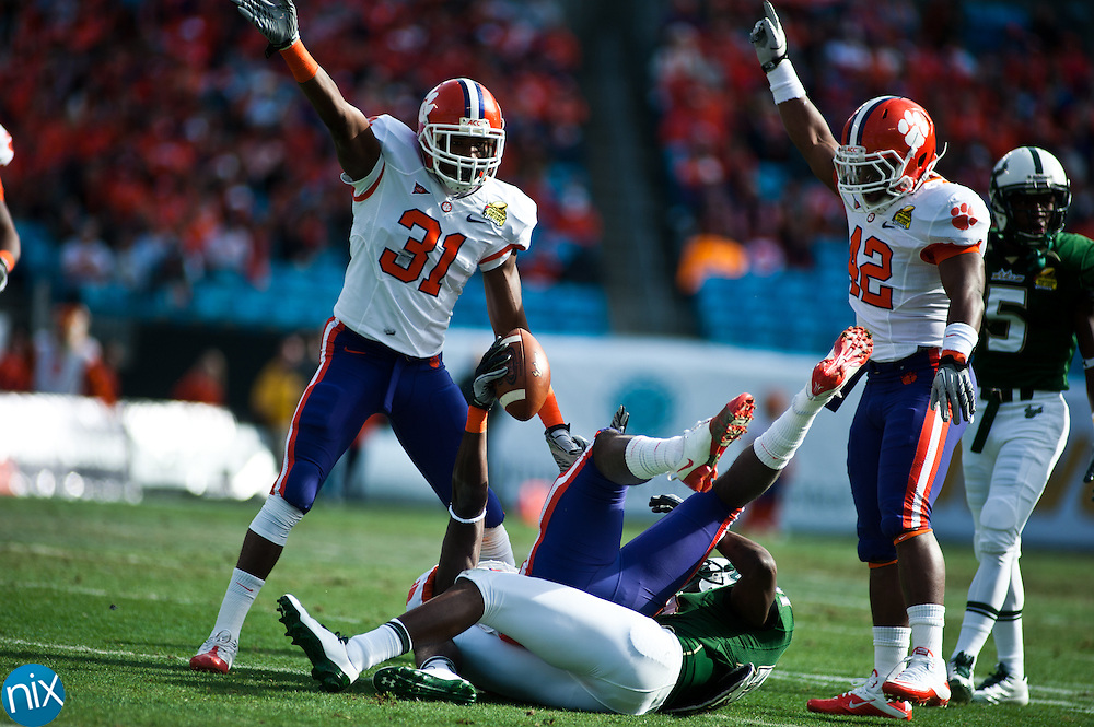 Clemson's Rashard Hall (31) and Corico Hawkins (42) signal an interception as Byron Maxwell holds up the ball during the Meineke Car Care Bowl at Bank of America Stadium Friday afternoon. The play was ruled an interception but South Florida won the game 31-26. (Photo by James Nix)