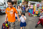 06 JUNE 2013 - BANGKOK, THAILAND:     A man and his daughter walk to school through Bobae Market in Bangkok. Bobae Market is a 30 year old market famous for fashion wholesale and is now very popular with exporters from around the world. Bobae Tower is next to the market and  advertises itself as having 1,300 stalls under one roof and claims to be the largest garment wholesale center in Thailand.       PHOTO BY JACK KURTZ