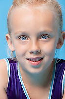 Close-up portrait of a young female gymnast over blue background