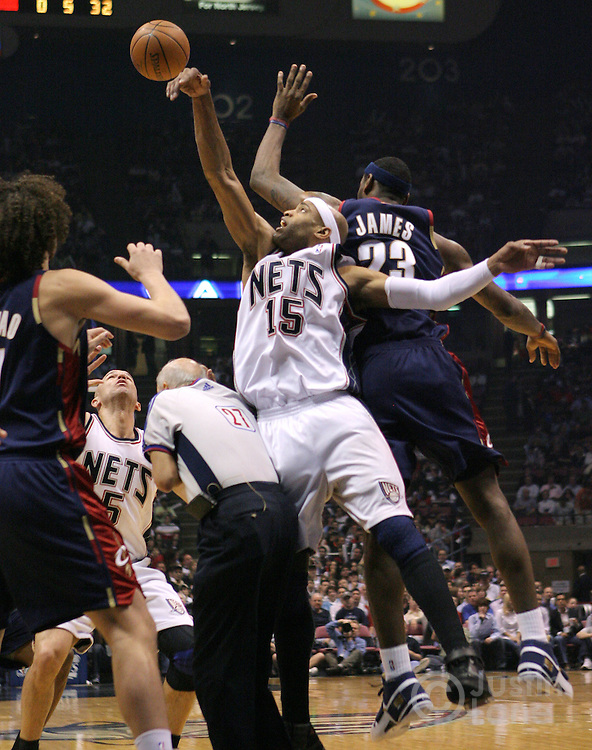 Nets' Vince Carter (2nd from R) reaches for the ball past the Cavaliers' LeBron James (R) over a referee (3rd from R) during the first half of game 4 of the Eastern conference semifinals between the Cleveland Cavaliers and the New Jersey Nets at Continental Airlines Arena in East Rutherford, New Jersey on 14 May 2007.