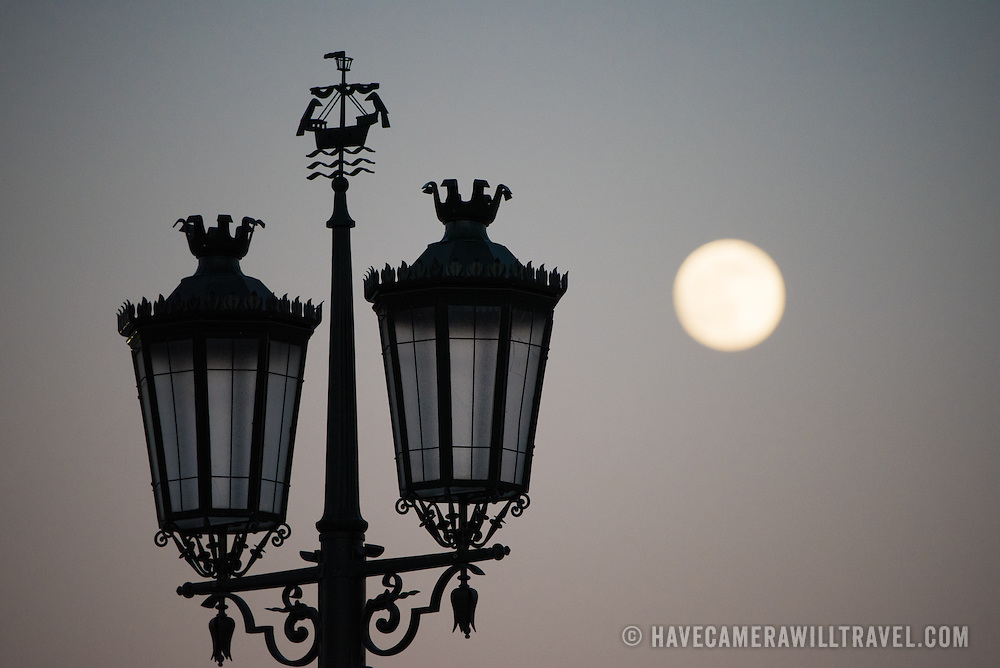 LISBON, Portugal - Silhouette of a street light on Praça do Comércio, with the full moon in the background. Known as Commerce Square in English, Praça do Comércio is an historic square in the Pombaline Downtown district of Lisbon, next to the Tagus River.