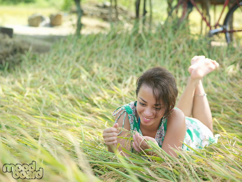 Young woman lying on meadow playing with grass smiling
