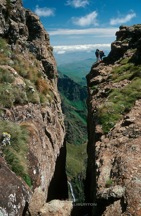 Hikers at a chasm in the Amphitheatre Wall, caused by erosion at a vertical fracture line in the basalt.  The Tugela Falls (visible below) drop 614m from this summit plateau elevation. Ukhahlamba-Drakensberg Park, KwaZulu-Natal, South Africa. Nikon F90; 35-135/3.5. Kodak E100SW. December 1996.