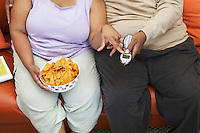 Couple sitting on couch with crisps and phone, mid section