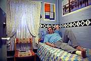 A prisoner watching Columbo in his decorated cell with a sprained ankle. HMP Coldingley, Surrey was built in 1969 and is a Category C training prison. Coldingley is focused on the resettlement of prisoners and all prisoners must work a full working week within the prison. Its capacity is 390 prisoners.