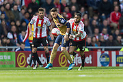 Arsenal midfielder Mesut Ozil (11) defends the ball from Sunderland's Midfielder Yann M'Vila (21) during the Barclays Premier League match between Sunderland and Arsenal at the Stadium Of Light, Sunderland, England on 24 April 2016. Photo by George Ledger.