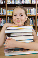 School girl hugging books in library, portrait