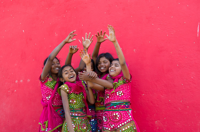 Happy and smiling young Indian girls in front of a pink wall (India)