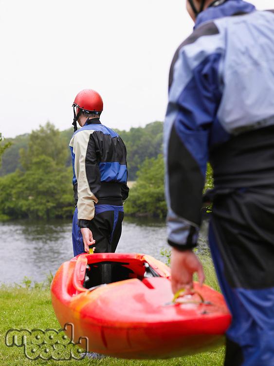 Two men carrying kayak to river