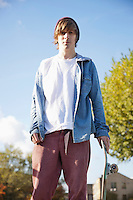 Portrait of serious young man with skateboard against sky