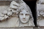 Mask and garland frieze from the Portico of Tiberius on the Southern portico of the Agora, 1st century AD, Aphrodisias, Aydin, Turkey. The Sculpture School at Aphrodisias was an important producer of carved marble sarcophagi and friezes from the 1st century BC until the 6th century AD. The Portico of Tiberius was built under the reign of Tiberius and has many examples of mask and garland friezes, consisting of the heads of gods, goddesses, theatrical characters, mythological figures or masks, each with a distinct facial expression, between hanging garlands of leaves, fruit and flowers. This example shows a sorrowful face. Aphrodisias was a small ancient Greek city in Caria near the modern-day town of Geyre. It was named after Aphrodite, the Greek goddess of love, who had here her unique cult image, the Aphrodite of Aphrodisias. The city suffered major earthquakes in the 4th and 7th centuries which destroyed most of the ancient structures. Picture by Manuel Cohen