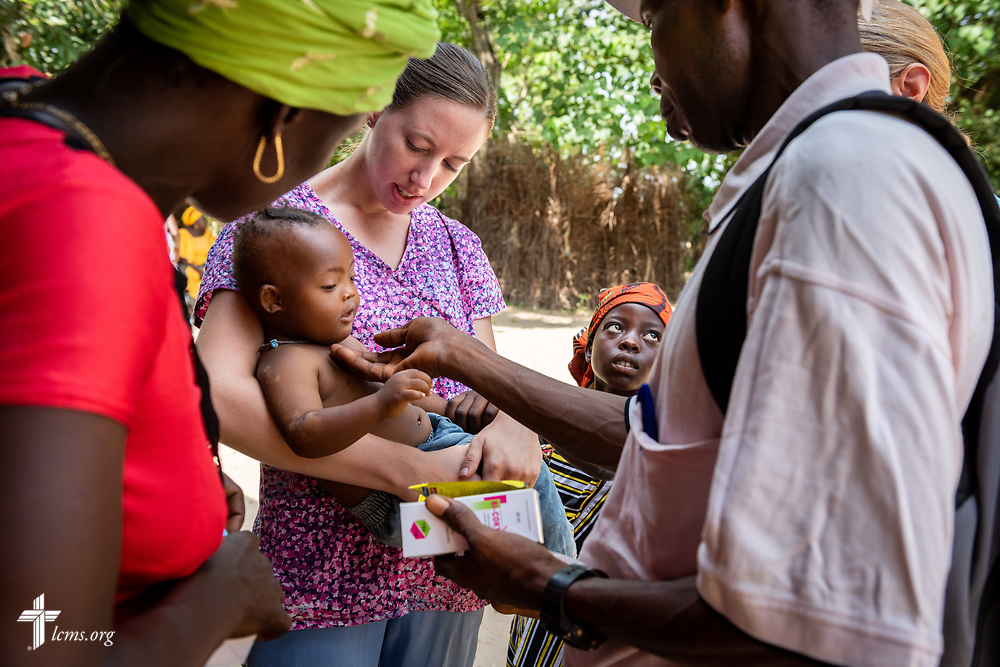 Molly Christensen, career missionary to Togo, carries a baby suffering from a very high fever on the fifth day of the LCMS Mercy Medical Team on Friday, May 11, 2018, in the Yardu village outside Koidu, Sierra Leone, West Africa. LCMS Communications/Erik M. Lunsford