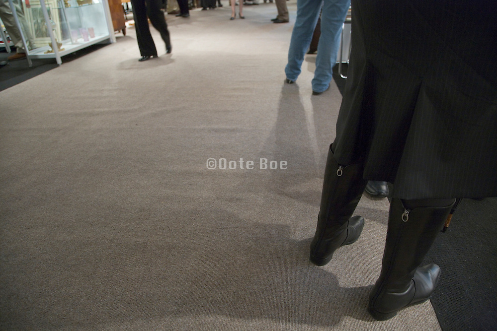 people's legs at an indoor art and design gallery fair event