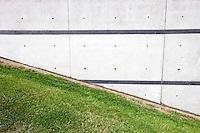 Green grass slope next to brick wall