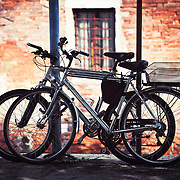 Two bikes resting against some poles in Venice, Italy.<br />