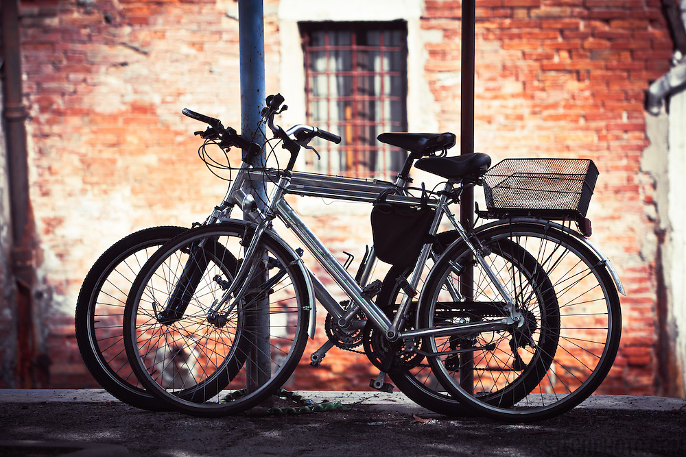 Two bikes resting against some poles in Venice, Italy.<br /> <br /> LICENSING: This image can only be licensed through SpacesImages. Click on the link below:<br /> <br /> http://tinyurl.com/cfno43x