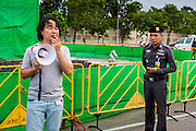 "24 JUNE 2014 - BANGKOK, THAILAND: A Thai police officer (right) listens to a poet at a meeting of the Monsoon Poets Society in Bangkok. Members of the ""Monsoon Poets Society"" gathered in front of the Anantasamakom Throne Hall Tuesday to pay homage to the People's Party, a Siamese (Thai) group of military and civil officers (which became a political party) that staged a bloodless coup against King Prajadhipok (Rama VII) and changed Thailand (then Siam) from an absolute monarchy to a constitutional monarchy on 24 June 1932. Since the coup against the civilian government on 22 May, the ruling junta has not allowed political gatherings. Although police read the poems, they did not arrest any of the poets or make any effort to break up the gathering.     PHOTO BY JACK KURTZ"