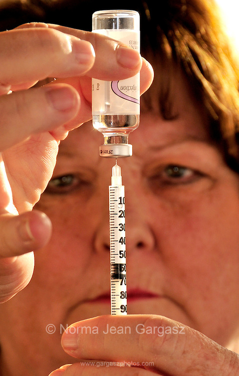 A chronically ill senior patient prepares a disposable syringe that she will use to to inject insulin in to her abdomen for treatment of type 2 diabetes.