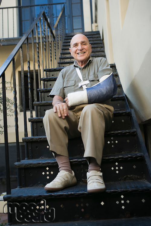 Man with broken arm sitting on stairs
