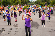 06 OCTOBER 2012 - BANGKOK, THAILAND: A public exercise class in Lumphini Park in Bangkok. Lumphini Park is 142 acre (57.6-hectare) park in Bangkok, Thailand. This park offers rare open public space, trees and playgrounds in the congested Thai capital. It contains an artificial lake where visitors can rent boats. Exercise classes and exercise clubs meet in the park for early morning workouts and paths around the park totalling approximately 1.55 miles (2.5 km) in length are a popular area for joggers. Cycling is only permitted during the day between the times of 5am to 3pm. Smoking is banned throughout the park. The park was created in the 1920's and named after Lumbini, the birthplace of the Buddha in Nepal.   PHOTO BY JACK KURTZ