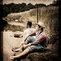 Huckleberry Finn and Jim standing by the mighty Mississippi River. Two fictional characters from the Adventures of Huck Finn by Samuel Langhorne Clemens AKA Mark Twain.