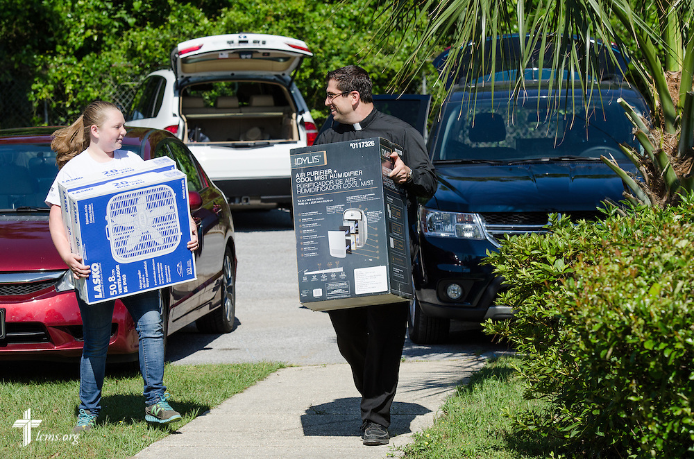 The Rev. Ross Johnson, director of LCMS Disaster Response, carries flood relief supplies to St. Matthew Lutheran Church with the help of Rosalyn Hadley, outside St. Matthew in Pensacola, Fla., on Saturday, May 3, 2014. Torrential rainfall led to widespread flooding in the area earlier in the week. LCMS Communications/Erik M. Lunsford