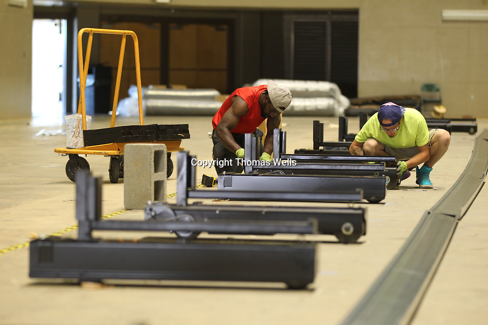 Bentre Riley, left, and Brandon Blakley begin to assemble the base for new the lower bowl seats being installed at the BancorpSouth Arena on Thursday.