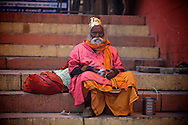 An old Sadhu sitting in a world of colours on the steps along the Ganges.<br />