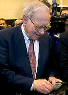 Omaha, Neb 5/6/06 Warren Buffet digs in his wallet to buy ice cream on the floor at the Berkshire Hathaway annual meeting in the Qwest Center Omaha Saturday Morning..(Chris Machian/For Bloomberg)