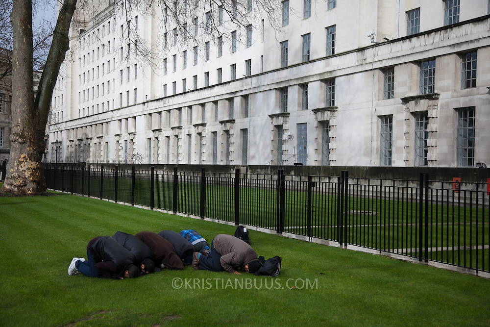 Devout muslims pray on the grass in Whitehall during speeches. An Anti-Assad Syrian demonstration held in Whitehall, Central London. The demonstration was called by the Syrian Community in the UK under the head lines; Syrians are being killed in a genocide and the world is watching. Several hundreds gathered opposite Downing Street 10 calling for Syrians to unite and the world to intervene.