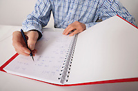Midsection of senior businessman writing in file at desk