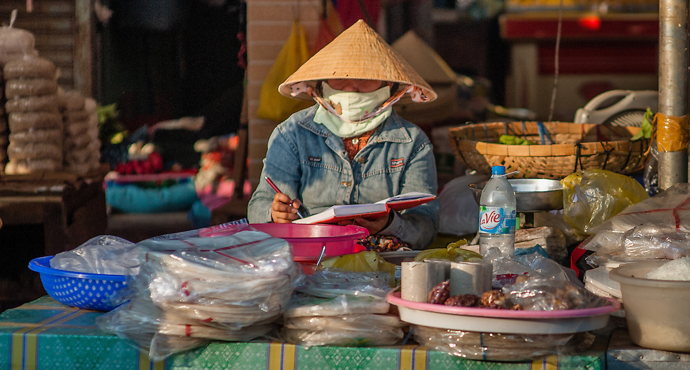 Woman with hat selling goods at market stall (Vietnam)